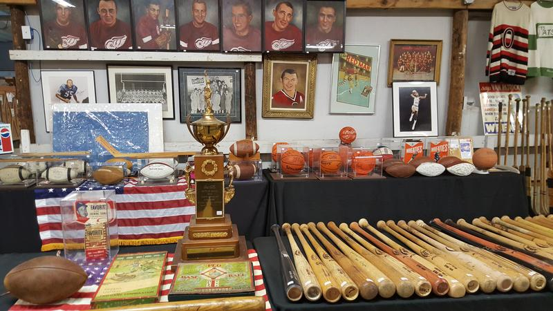Collection of autographed baseball bats and hockey sticks
