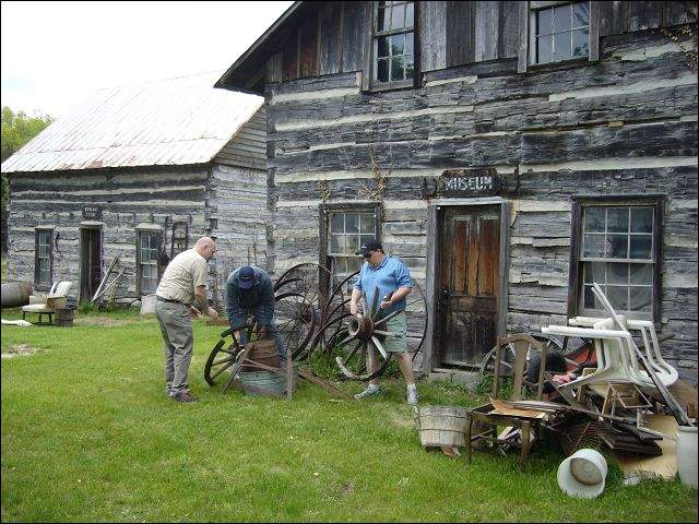 Scott Adkins, Brian Adkins and auctioneer Kenny Lindsay (from left to right) assemble an antique wagon wheel at the  Rustic Village Museum in Waltz. The museum and a general store (building at far left), both made of logs was sold at an auction handled by Ken Lindsay of American Eagle Auction & Appraisal Company.